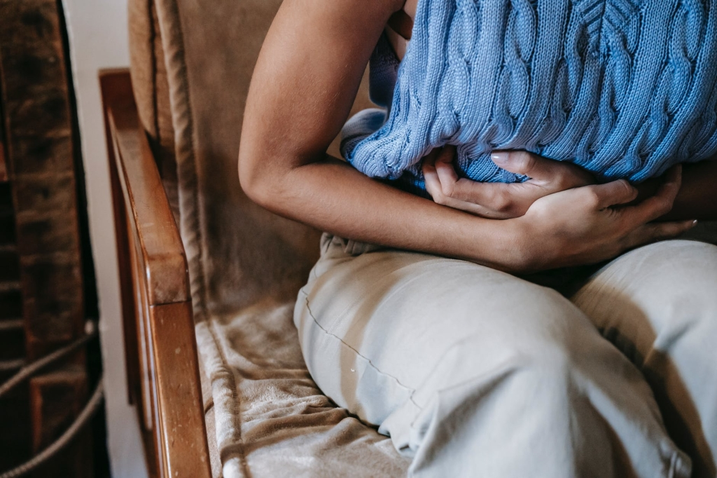 Woman holding her stomach with cramps